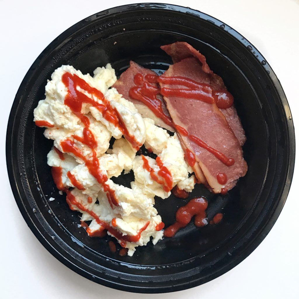 Weekly meal prep breakfast of scrambled egg whites and turkey bacon with a drizzle of sriracha